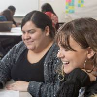 Two students laughing and working together on an in-class assignment.